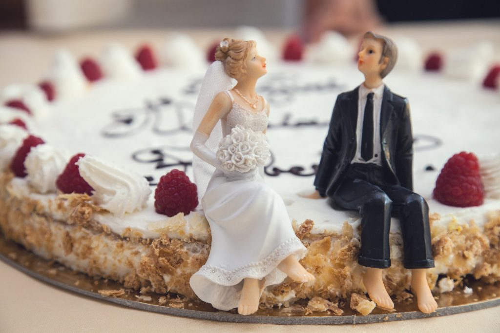 Cake topper figurines of a married couple sitting on a cake.